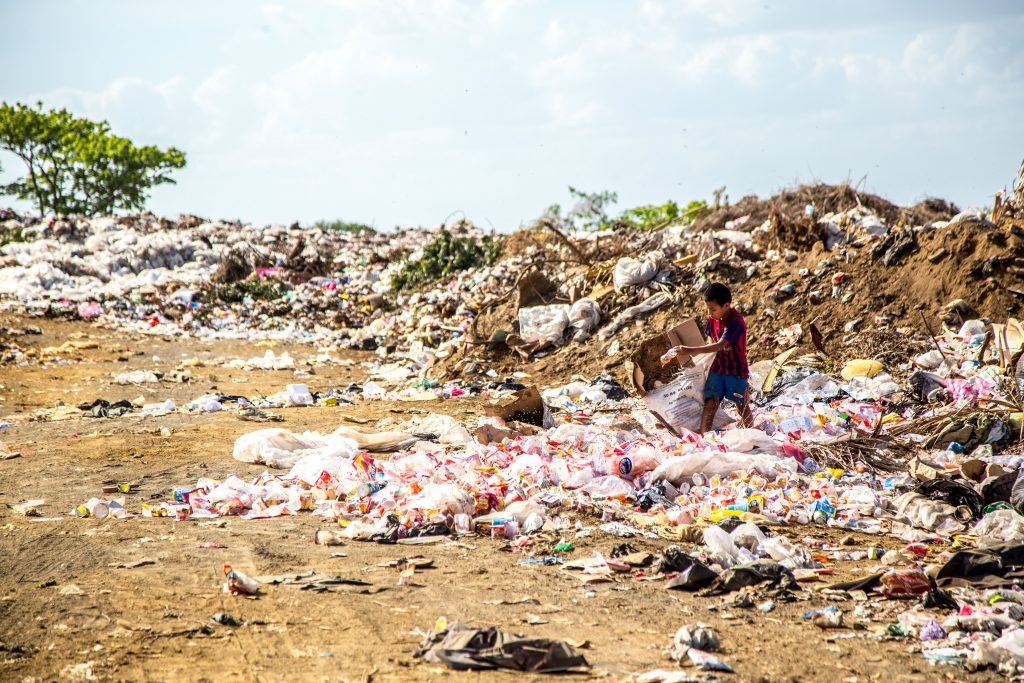 child surrounded by plastic pollution